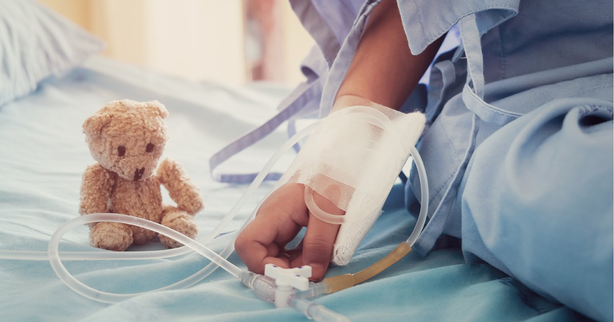 Arm of child on hospital bed with teddy bear