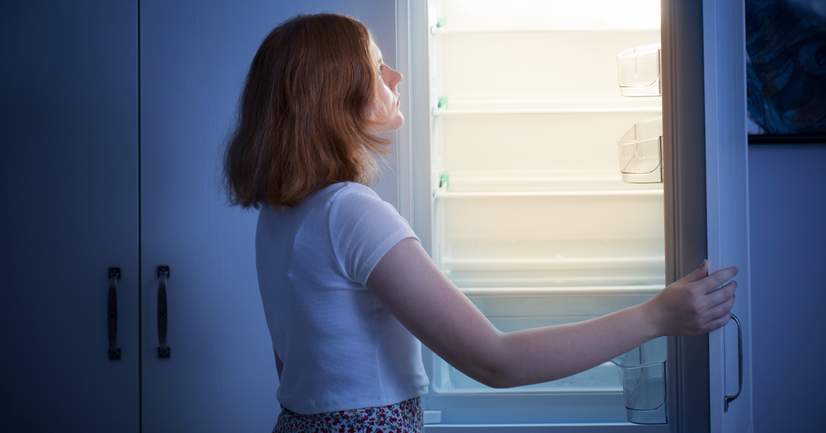 Woman sadly looking into refrigerator