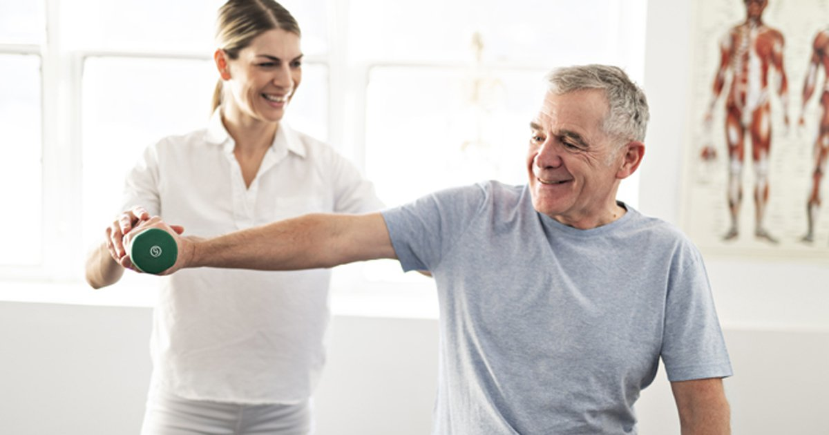 Man being assisted in weight lifting