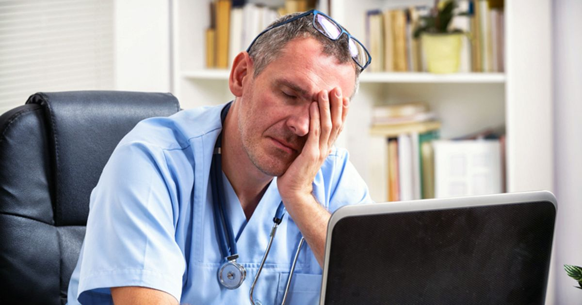 stressed doctor with head in hands